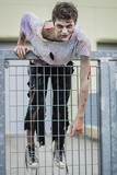 One teenage male zombie climibing gate in city setting in the evening, looking at camera. Halloween theme