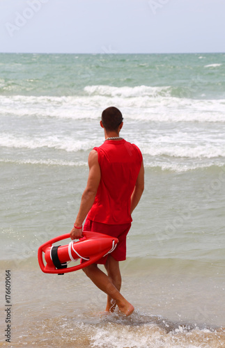Póster muscular lifeguard at shore at the sea shore in the beach of the