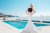 Beautiful blonde young slim woman model girl standing next to an exclusive pool and spa Willas in a long wedding dress carnival ballroom polka-dots in the island of Santorini spain - 176609872