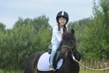 Little girl riding a pony - 176626292