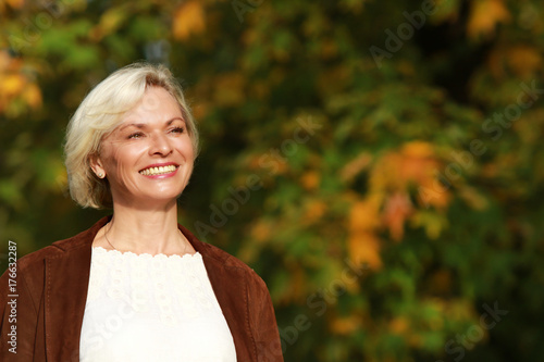 Poster Happy mature woman in front of golden autumn leaves