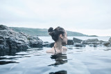 Young cheerful girl swimming in water of pool looking away on background of sea, Iceland, West Fjords. back view, Woman washing and covering her face with her hands - 176635634