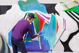 Artists draw graffiti on a fence. - 176645641