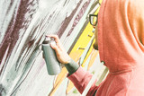 Street artist painting graffiti with color spray his art on the wall  - Young man writing and drawing murales on the street - Urban lifestyle and contemporary art concept - 176648273