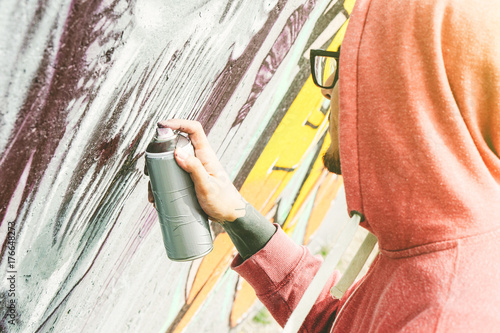 Street artist painting graffiti with color spray his art on the wall  - Young man writing and drawing murales on the street - Urban lifestyle and contemporary art concept