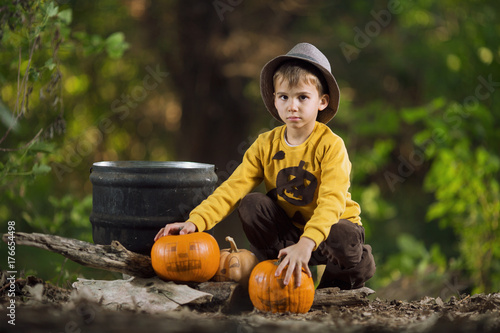 Little boy in Halloween costume with pumpkins in the forest