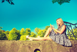 Woman sitting in park, relaxing and using phone - 176669238