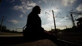 Silhouette of man sitting on edge of railroad platform and talking on phone - 176673020