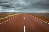 Straight line highway Australian landscape with dramatic clouds in Central Australia