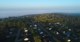An early foggy autumn morning establishing shot over a typical New England residential neighborhood.  	 - 176676082