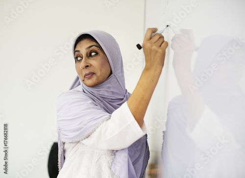 Muslim teacher writing on a white board Poster