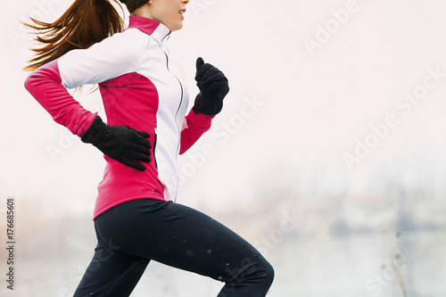 Winter running athlete woman on cold run jogging fast with speed and sprint on outside workout wearing warm clothing gloves, winter tights and wind jacket in snow weather.