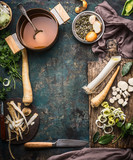 Vegetables soup cooking preparation with parsnip and leek on rustic kitchen table background with ingredients, pot , vegetable broth, knife and cutting board, top view, frame - 176690436