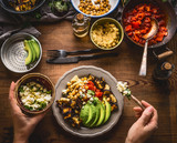 Female woman hands served healthy vegetarian meal in bowl with chick peas puree, roasted vegetables , red paprika tomatoes stew, avocado and seeds . Clean eating, dieting, vegetarian food concept - 176690646