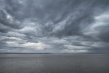 Landscape image of view out to sea with storm cloud sky overhead - 176691242