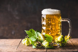 Beer mug with cap of  foam on table with fresh hops at dark rustic background, front view - 176695207