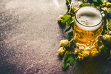 Beer mug with foam on table with fresh hops at dark rustic background - 176695243