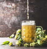 Beer pours into mug on table with fresh hops at dark rustic wall background, front view - 176695292
