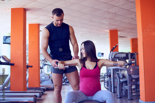 Fotobehang Fitness Young pregnant woman lifting dumbbells on fitball