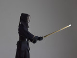 Portrait of man kendo fighter with shinai (bamboo sword). Studio shot