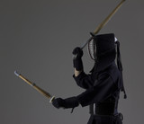 Man is practicing kendo in traditional armor .He swinging with two bamboo swords.