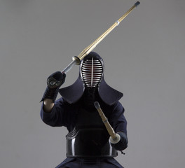 Man is practicing kendo in traditional armor .He swinging with two bamboo swords