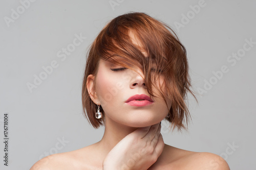 Foto op Canvas Kapsalon Hairstyle advertising. Beauty girl portrait. Female introvert closeup, modern fashion look, young woman with clean skin on grey background. Dreams, calmness, healthy mind concept