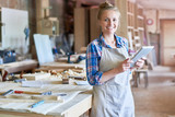 Portrait of happy young woman looking at camera using digital tablet in modern woodworking shop, copy space - 176718275