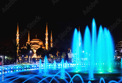 Colorful illuminated fountain on the background of the Sultanahmet Blue Mosque i Poster