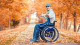 lebensfroher Rollstuhlfahrer im Park - 176722872
