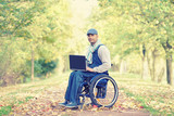 erfolgreicher Rollstuhlfahrer mit Laptop im Park - 176723294