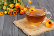 Calendula tea with fresh flowers on black wooden background
