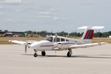 red white and blue dual propeller aircraft stationary on the airport tarmac
