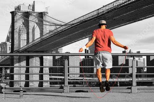 Fotobehang Fitness Morning exercises with skipping rope on the background of the city