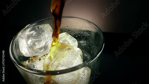 pouring of fresh coke in the drink glass with ice cubes on black background, fun and summer time concept