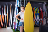 Woman is posing with surfboard in store on the beach. - 176746294