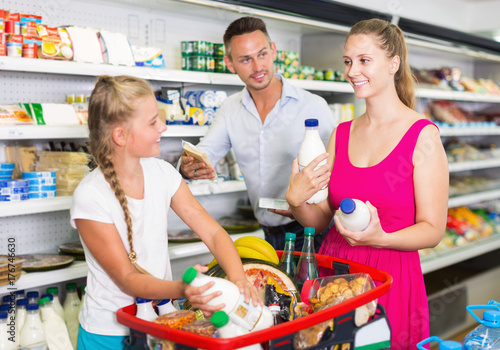 Smiling young woman with family choosing milk