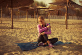 Beautiful woman resting after jogging on the beach at sunset and holding bottle of water - 176750008