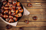chestnuts in a pan on wooden background - 176764072