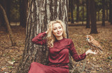 beautiful romantic girl with blonde hair and in a burgundy dress holding an owl in her hand in the woods - 176765468