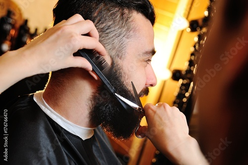 Barber or a hairdresser cuts hair and beard to a man in a hairdresser or a barbershop