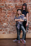 Urban style. Friendship in hip hop. Stylish female teenagers in studio, happiness in dance, brick wall background with free space. Happy street life, beautiful sisters concept