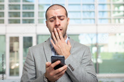 Concerned man looking at his mobile phone