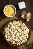 Homemade fresh savory popcorn with cheese, garlic and dried oregano in wooden bowl, photographed overhead on dark wood with natural light (Selective Focus, Focus on the top of the popcorn) - 176786845