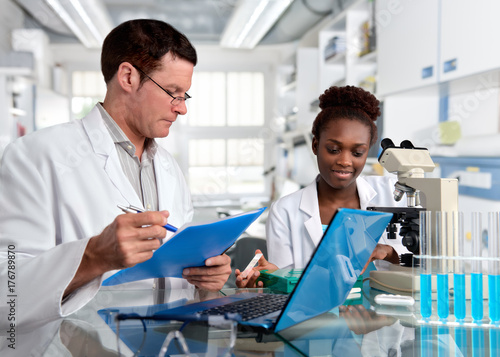 Poster Scientists, Caucasian male and African female, work in laboratory