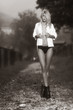 Sexy blonde naked girl with a white shirt posing along a path - black and white outdoor with nature on te background