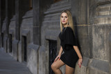 Young blonde woman wearing black dress on street - 176813437