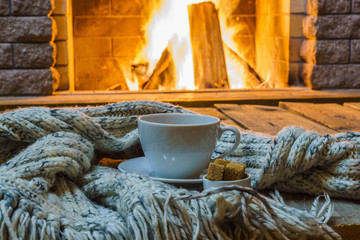 Cup of tea and sugar, woolen things near cozy fireplace, in country house, winter vacation, horizontal.