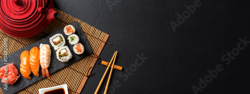 Canvas Sushi bar Set of sushi with wasabi, soy sauce and teapot on black stone background