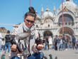 Young female traveler sitting and feeding pigeons on the Piazza San Marco